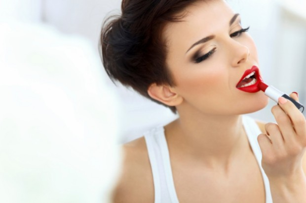 Beautiful Brunette applies lipstick.  Lipgloss and Brush. Red li